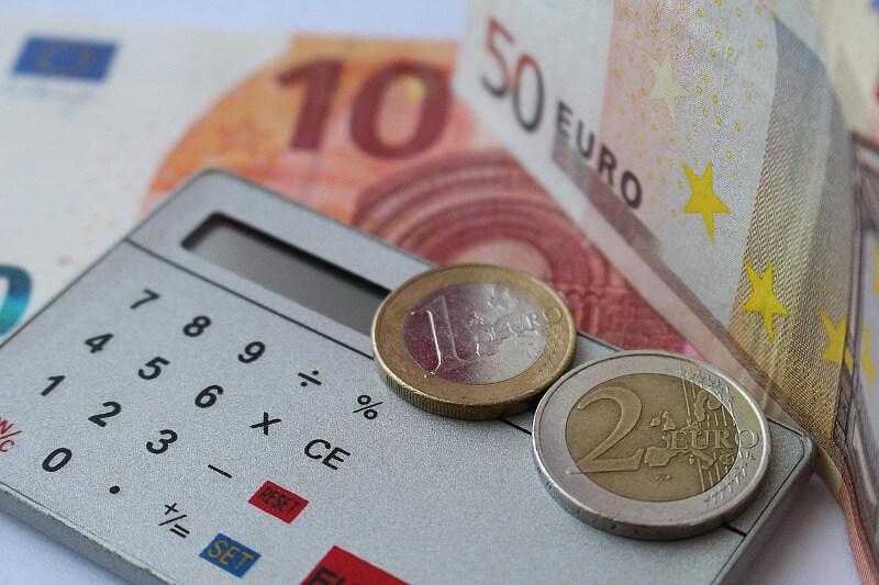 Risikolebensversicherung, Beitragszuschlag bei Bluthochdruck (Hypertonie), Taschenrechner mit Münzen