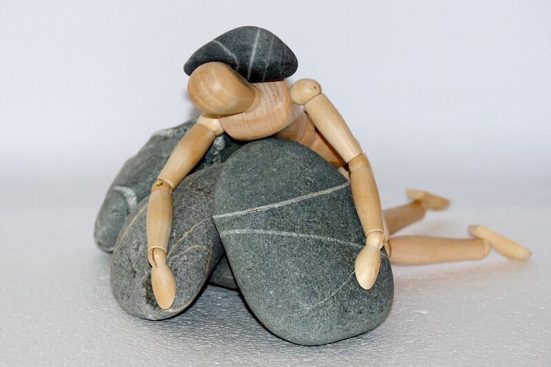 Risikolebensversicherung Abschluss bei Depression, Holzfigur unter Steinen
