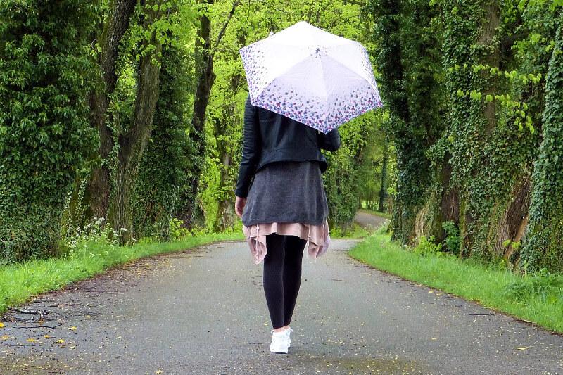 Junge Frau spaziert mit Regenschirm bei Pollenflug