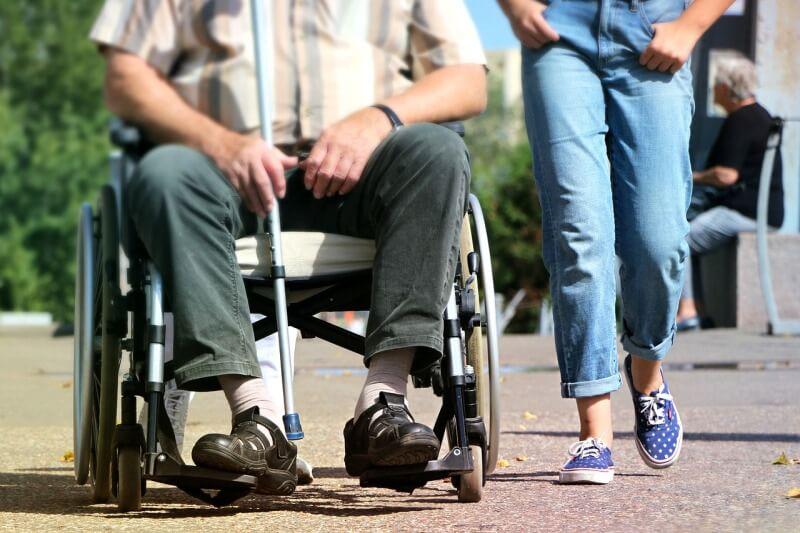 Mann im Rollstuhl wird von einer anderen Person begleitet