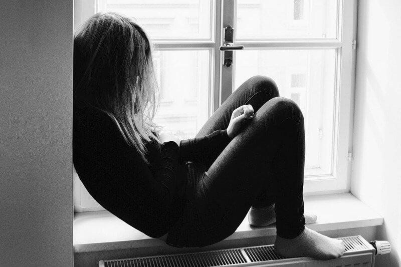 Junge Frau sitzt auf einer Fensterbank