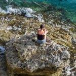 Frau sitzt alleine am Meer
