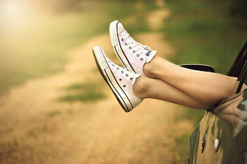 Eine Frau streckt ihre Beine aus dem Autofenster.
