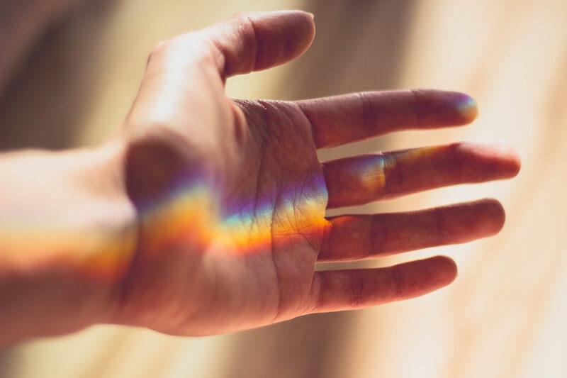 Hand mit Lichteinfall in Regenbogenfarben